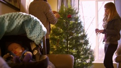 Baby sleeps while mom and dad decorate the Christmas tree Stock Footage