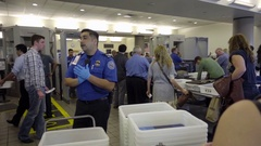 TSA inspectors and travelers putting baggage on conveyor belt at LAX airport LA Stock Footage