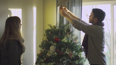 Young man puts a star ornament on the top of the Christmas tree Stock Footage
