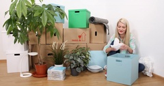 A Happy Woman Unsealing a Fragile Pottery and Remove Paper New House Living Room Stock Footage