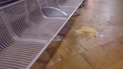 Vomit on floor next to public bench at train station, Berlin, Germany Stock Footage