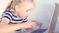 Little European girl to have fun and work at the computer Stock Footage