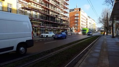 Yellow tram train arrives at station platform, cars, road, Berlin, Germany Stock Footage