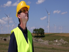 Engineer  Man Looking at Wind Turbines and Blueprint Analyzing Power Generator Stock Footage
