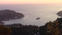 Big military vessel moored by a peninsula at sunset Stock Footage