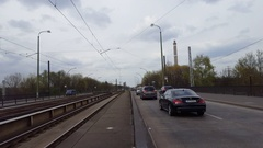 Cars drive into Berlin, tram train tracks, industrial factory chimney, Germany Stock Footage