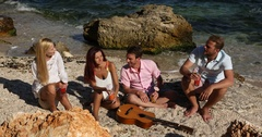 Joyful Young Group People Drink Juice Cheerful Friends Sing Music Guitar Beach Stock Footage