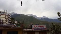 Himalaya mountain snow peaks, clinic sign, Mcleod Ganj, Dharamsala, India Stock Footage