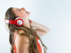 Beautiful young girl listening to music on headphones Stock Photos