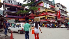 Busy main intersection, people, cars, hotels, restaurants, Mcleod Ganj, India Stock Footage