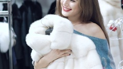 Beautiful girl chooses a fur coat in the shop Slowly Stock Footage
