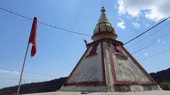 Small Hindu shrine temple with flags, low angle sky, Himalayas, India Stock Footage