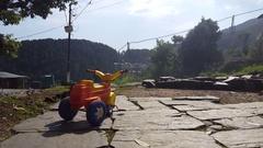 Small baby child tricycle in Himalaya mountain village, Bhagsu, India Stock Footage