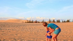 Backside Mother Small Girl Join Hands Run on Dunes at Sunset Stock Footage