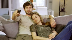Man laughing watching tv at home on sofa with sleepy girlfriend Stock Footage