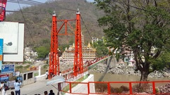 Lakshman Jhula bridge over Ganges river, busy people cross, Rishikesh, India Stock Footage