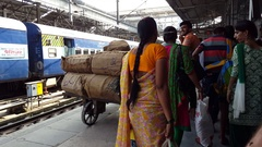 Porters carry heavy parcels, people on platform, Amritsar Train Station, India Stock Footage