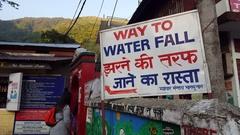 People follow Way To Waterfall sign, Hindi English, Bhagsu, Dharamsala, India Stock Footage