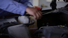 Mechanic under hood- Checking oil, dipstick with red rag under hood Stock Footage