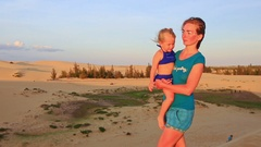 Closeup Mother Carries in Arm Small Girl against Dunes at Sunset Stock Footage