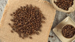 Tabletop of roasted coffee beans rotating on burlap. Rustic wooden background Stock Footage