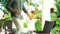Young, happy man relaxing and drinking beverage sitting by table in garden Stock Footage