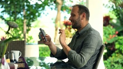Young, happy man chatting on smartphone sitting in garden Stock Footage