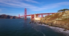 Low Angle Over Water And Rocks At Shore Moving Toward Golden Gate Bridge 4K Stock Footage