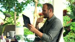Young, happy man chatting on tablet and drinking beverage in garden Stock Footage