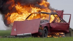 Car bomb after it exploded with parts in the air Stock Footage
