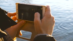 Taking a picture with a smartphone by the river at sunset Stock Footage