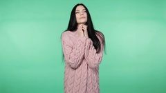 Young brunette woman wrapping up in a pink cardigan Stock Footage