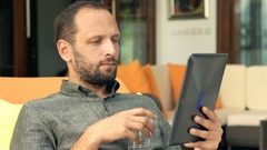 Young man reading news on tablet and drinking water lying on lounger on patio Stock Footage