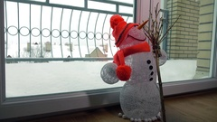 Funny toy handmade snowman against snowstorm behind the glass door. 4K shot Stock Footage