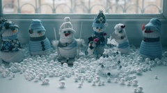 Several toy handmade snowmen and snowstorm outside the window. 4K tilt shot Stock Footage