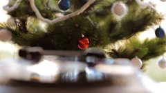 In vintage gramophone playing a vinyl record on a background of Christmas tree. Stock Footage