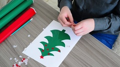 Boy making Christmas card from self-adhesive papers Stock Footage