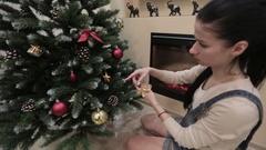 Beautiful Girl Hangs Up Toy On Christmas Tree Stock Footage