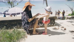 Pretty girl rubs baby with sunscreen Stock Footage