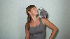 CLOSE UP: Young girl with African grey parrot on shoulder singing and dancing Stock Footage