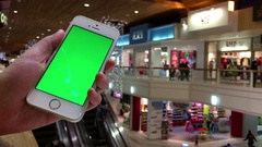 Woman holding green screen cell phone beside escalator Stock Footage