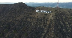 Aerial moving toward and over big Hollywood sign letters at sunset in 4K Stock Footage