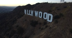 Aerial tracking and rising over Hollywood sign to hills at sunset in LA CA 4K Stock Footage