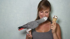 CLOSE UP: Portrait of beautiful girl and African grey parrot eating icecream Stock Footage