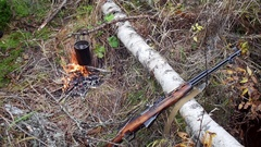 Boiling water in pots above the fire in outdoor. Hunter shotgun Stock Footage
