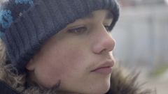 Close-up of a good-looking teenage boy wearing a hat and parka on a cold day. 4K Stock Footage