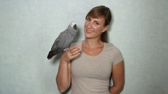 CLOSE UP: Portrait of lovely African grey parrot sitting on young girl's fingers Stock Footage