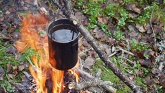 Boiling water in pots above the fire in outdoor Stock Footage