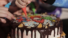 Children decorate a Christmas cake. close-up Stock Footage