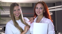 Two sexy office collaborators poses for the camera with a sheet of white paper Stock Footage